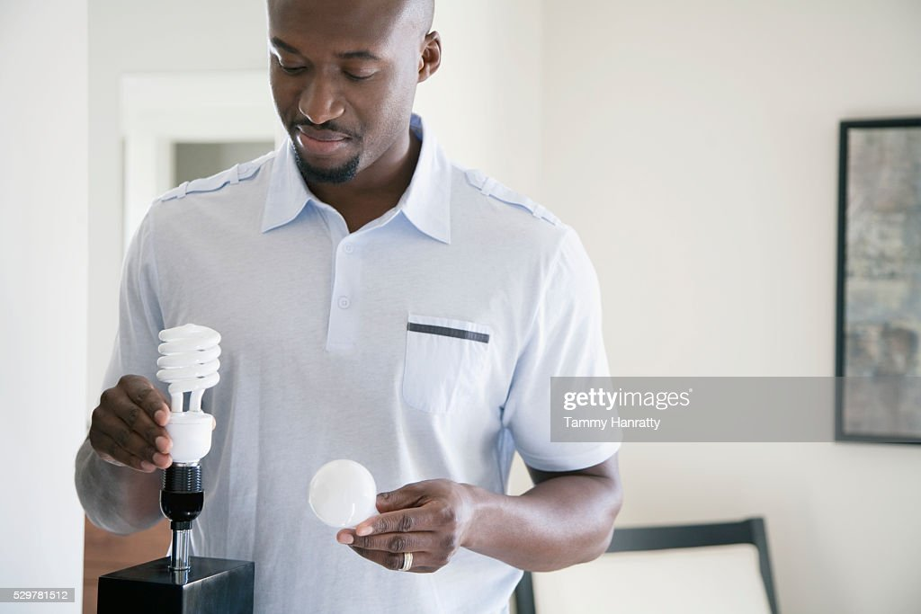 Man holding old and new light bulbs : Stock Photo