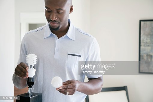 Man holding old and new light bulbs : Stock-Foto