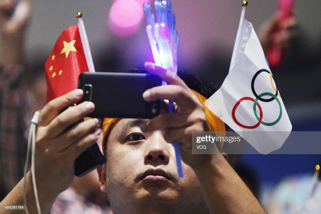 A man holding Olympic flag and Chinese flag takes photos during the closing ceremony of 2014 Summer Youth Olympic Games at Nanjing Olympic Sports Centre on August 28, 2014 in Nanjing, China.