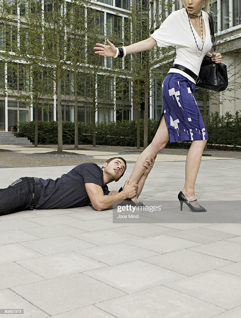 man holding onto womans leg, as she walks away : Stock Photo