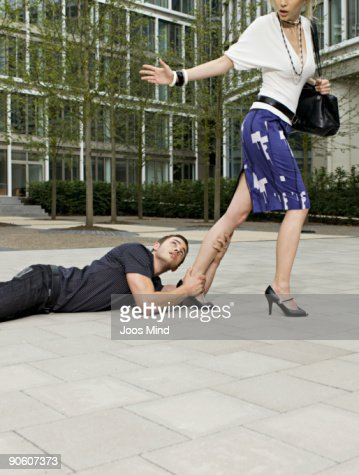 man holding onto womans leg, as she walks away