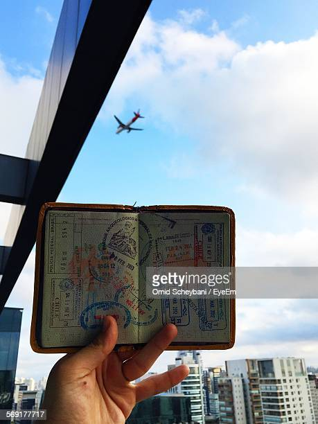 Man holding open passport, cityscape and airplane in background