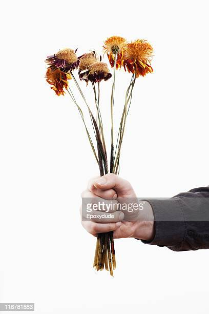 A man holding out a bunch of dead flowers, close-up of hand