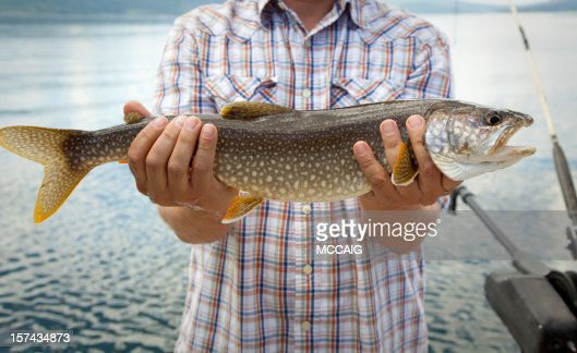 A man holding out a trout that he caught