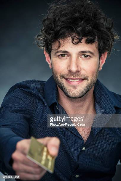 Man holding out credit card and smiling, portrait