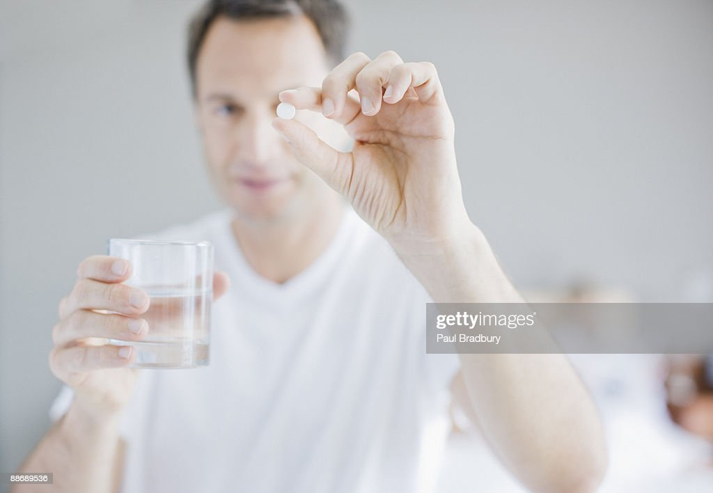 Man holding out medicine tablet : Stock Photo