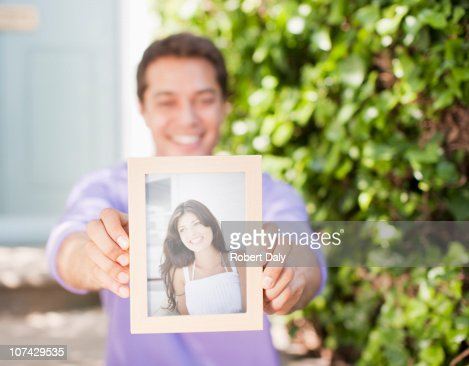 Man holding out photograph of girlfriend : Stock Photo