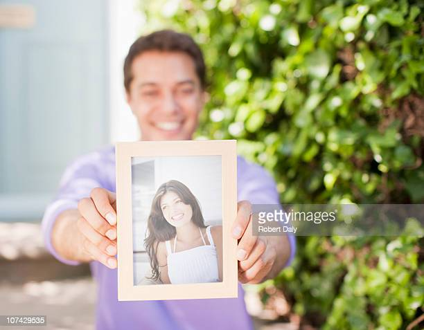 Man holding out photograph of girlfriend