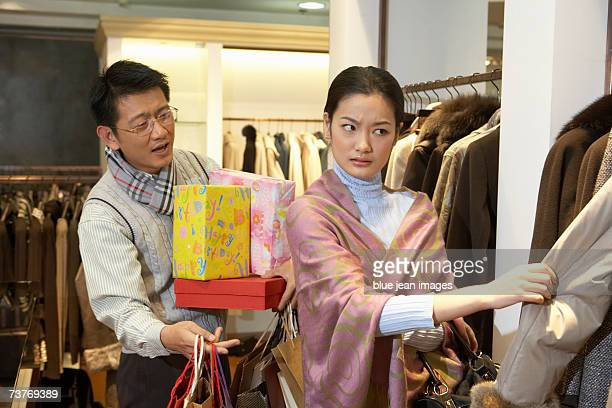Man holding packages looks distressed as perturbed woman continues to shop