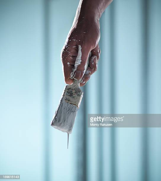 Man holding paint brush with white paint dripping
