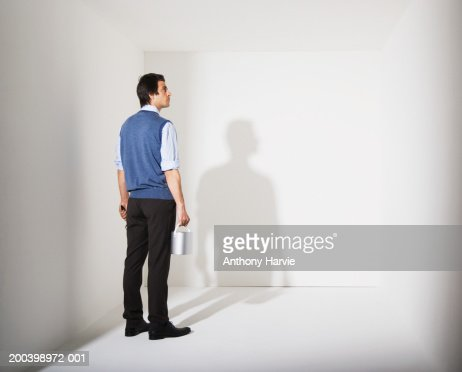 Man holding paint bucket in white room : Stock Photo