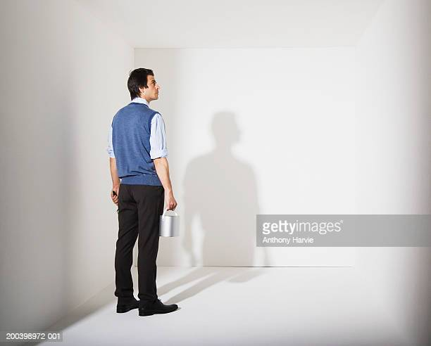 Man holding paint bucket in white room