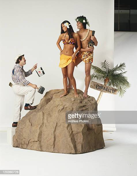 Man holding paint tin and brush looking at hula couple on rock, smiling