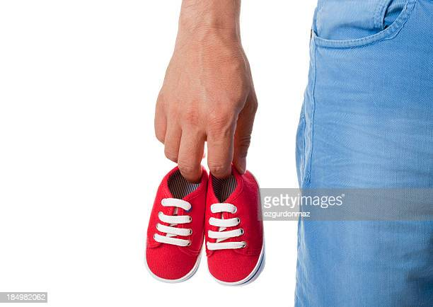 Man holding pair of baby shoes