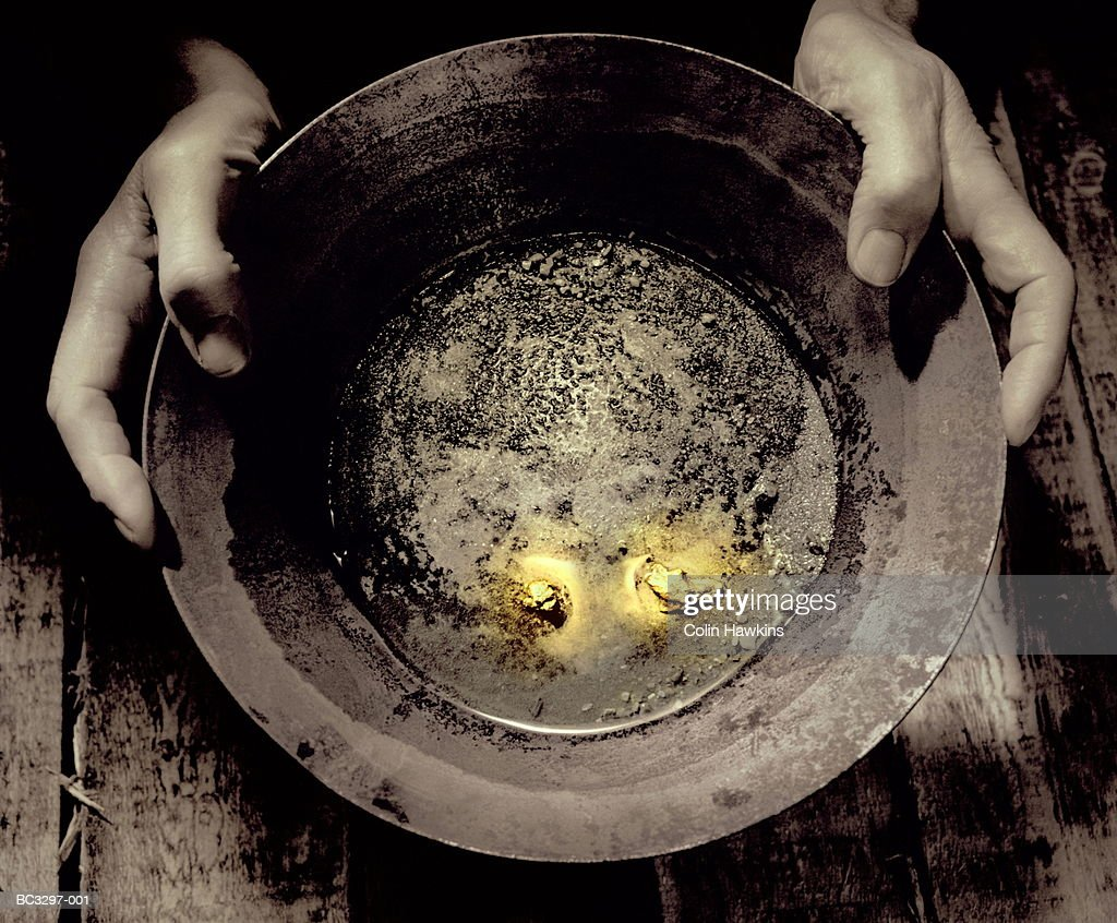 Man holding pan containing nuggets of gold, close-up (tinted B&W)