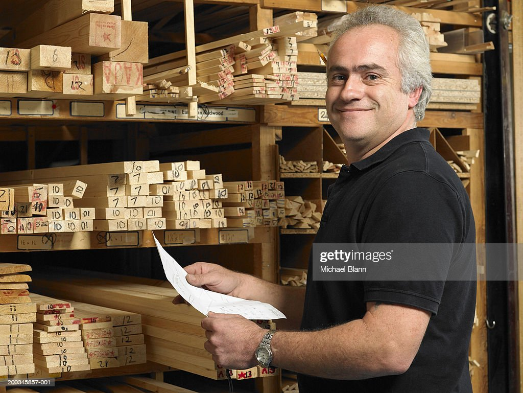 Man holding paper by planks of wood on shelves, smiling, portrai
