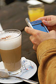 Man holding PDA, with glass of coffee latte on table
