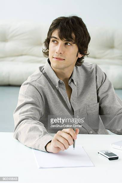 Man holding pen above paper, looking away
