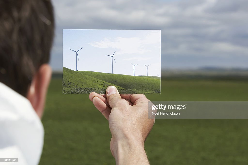 man holding picture of windmills against landscape : Stock Photo