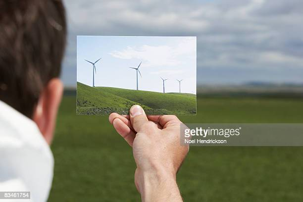 man holding picture of windmills against landscape