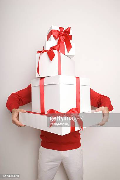 Man Holding Pile of Presents Stacked High