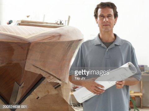 Man holding plans in boat building workshop, portrait : Stock Photo