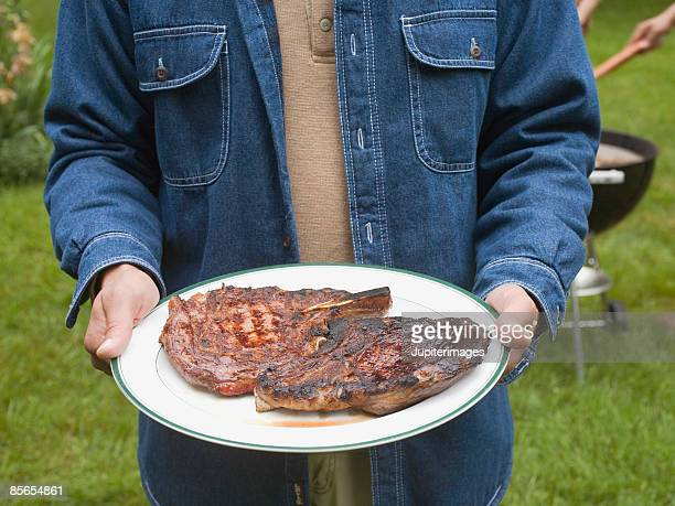Man holding plate of barbecue