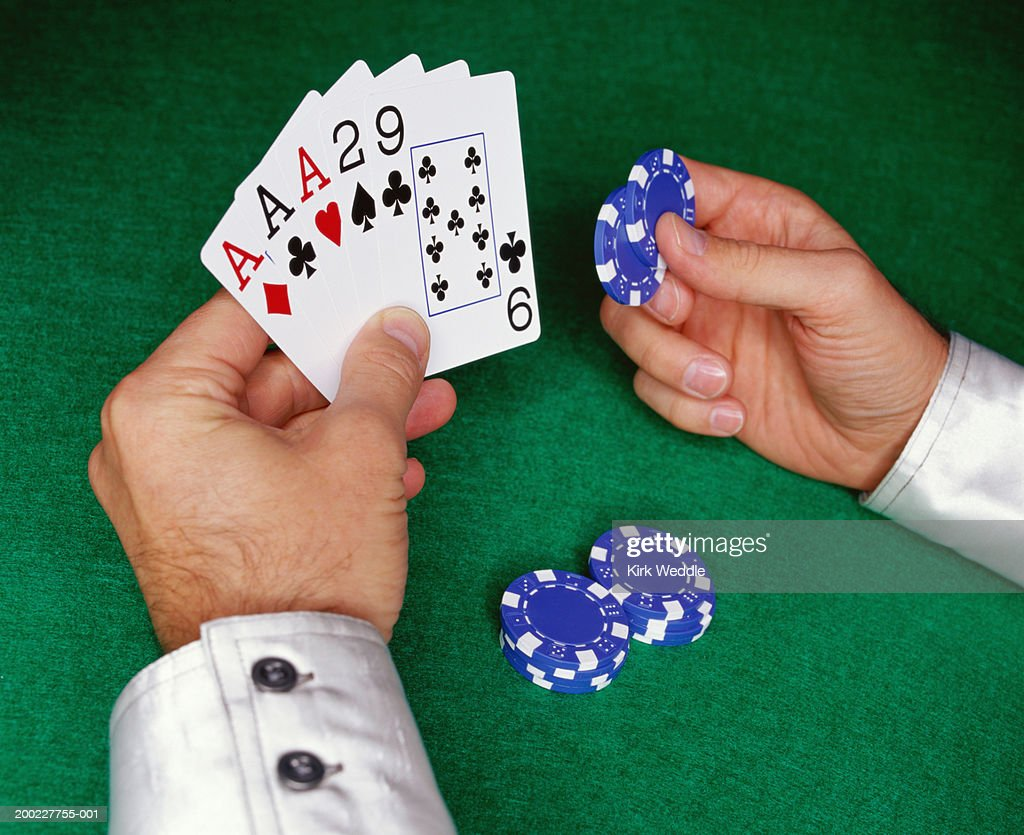 Man holding playing cards and poker chips, close-up of hands : Stock Photo