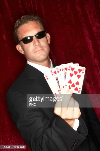 Man holding playing cards, showing royal flush, portrait : Stock Photo