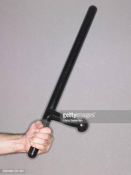 Man holding police baton, side view