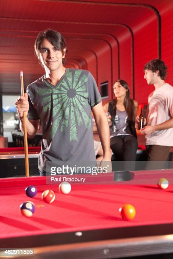 Man holding pool cue by pool table and smiling : Stock Photo