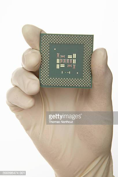 Man holding processor chip, wearing latex glove (focus on chip)