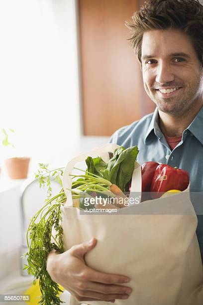 Man holding produce in canvas bag