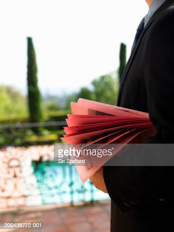 Man holding real estate flyers (mid section)
