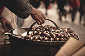 Man holding roasted chestnuts