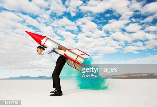 Man holding rocket on his back in desert.