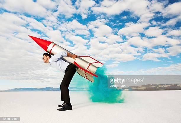 Man holding rocket on his back in desert.