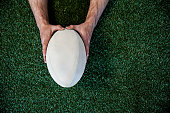 Man holding rugby ball over the grass