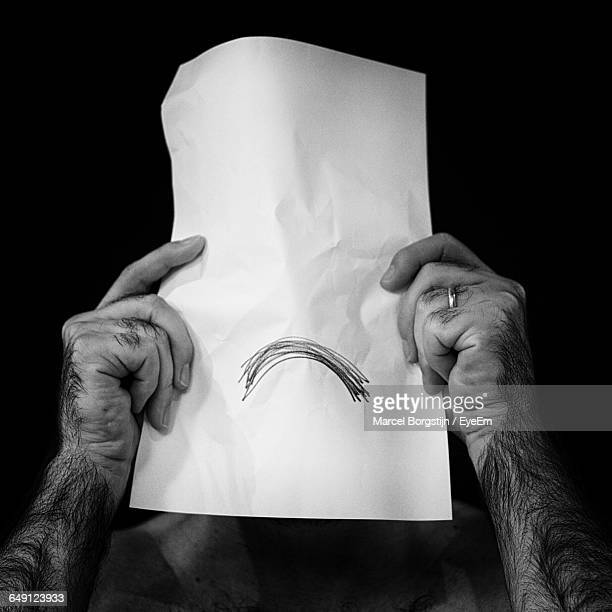 Man Holding Sad Face In Front Of Face Against Black Background