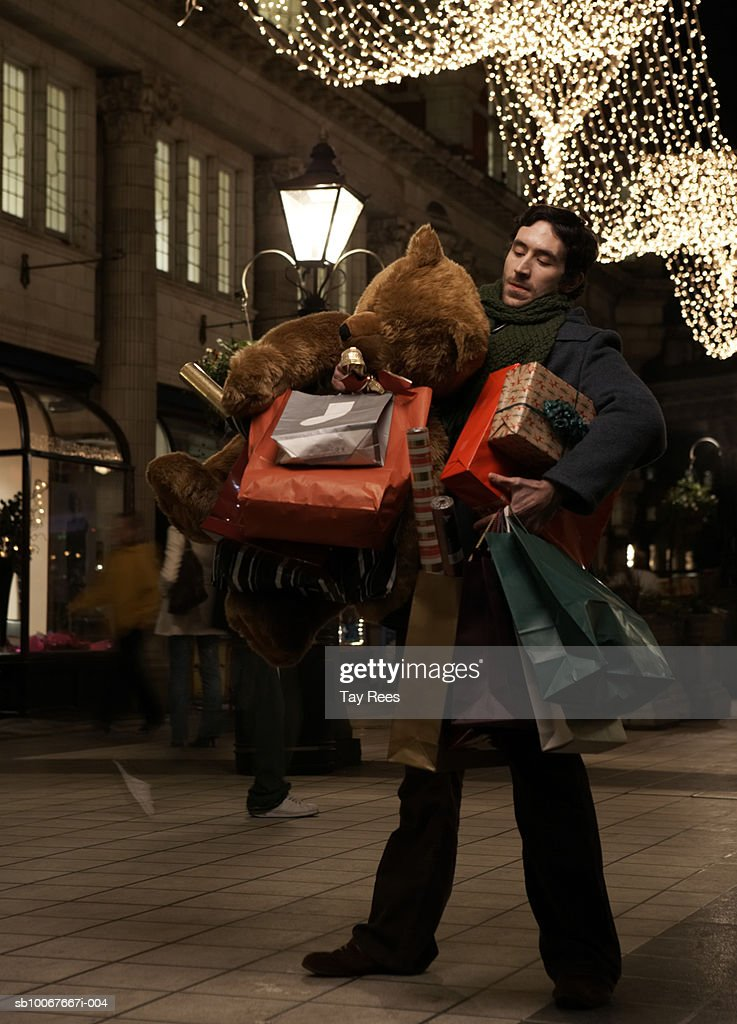 Man holding shopping bags and giant teddy bear, standing on street at night : Stock Photo