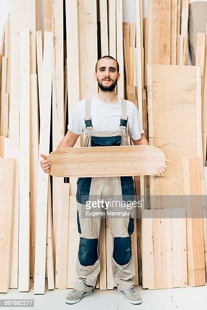 Man holding skateboard in workshop