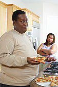 Man holding slice of pizza, woman watching from behind