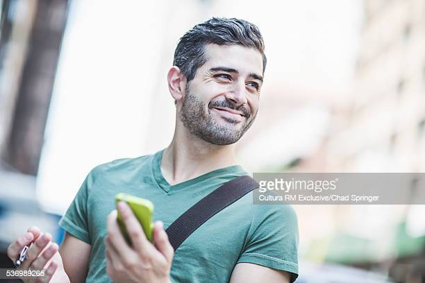 Man holding smartphone in street