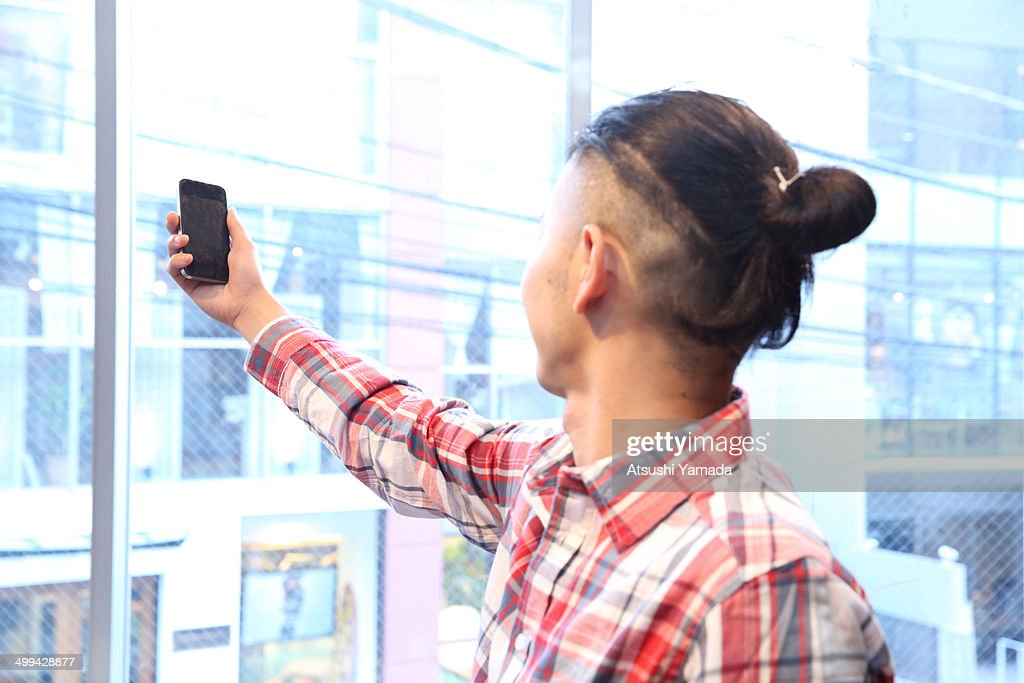 Man holding smartphone near window