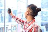 Man holding smartphone near window