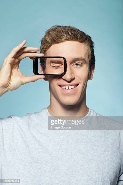 Man holding smartphone over eye