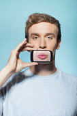 Man holding smartphone over mouth