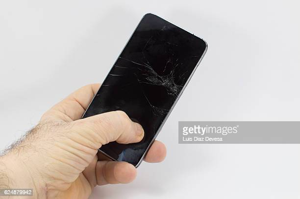 man holding smartphone with torn screen