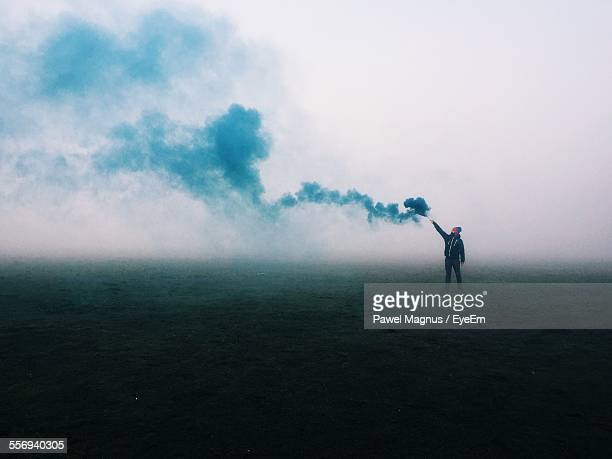 Man Holding Smoke Bomb On Field In Foggy Weather