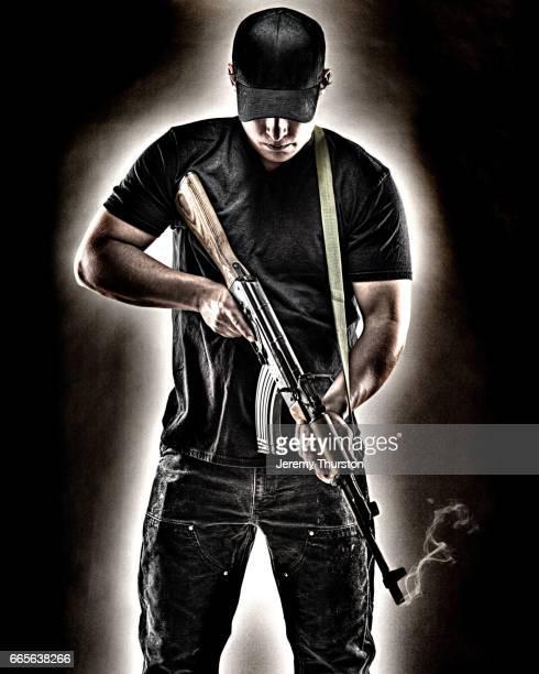 Man holding smoking assault rifle